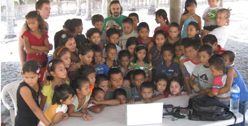 The kids of El Tamarindo crowd around a laptop computer