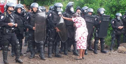 an elderly El Salvadorian women stands up to a line of riot police in armour