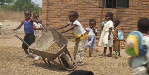 Children playing with a wheelbarrow