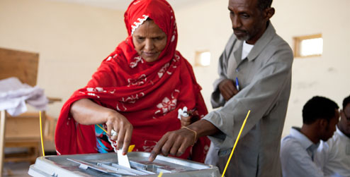 Woman puts voting slip in box at polling station in Somaliland