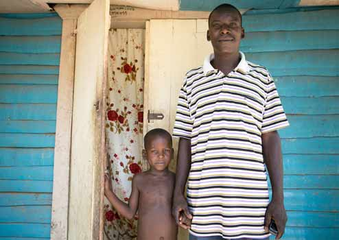 Oranus and his son outside their home in Gens de Nantes, Haiti. (©Fran Afonso/Progressio)