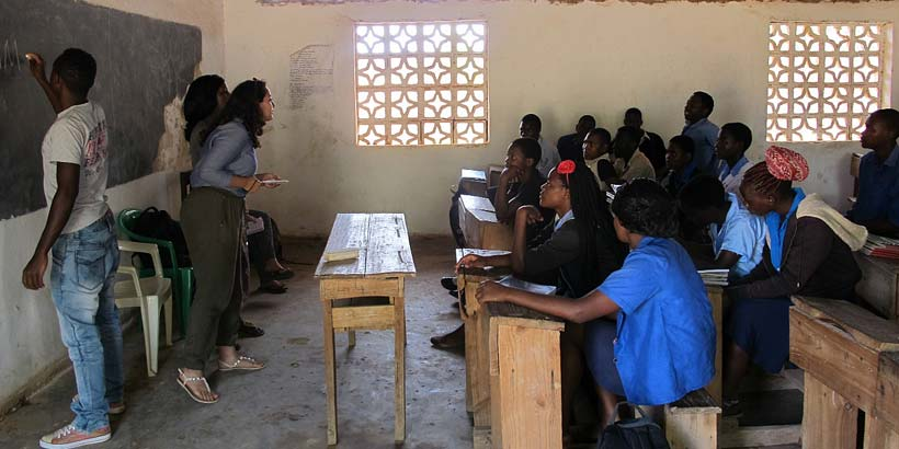 Ikram facilitating a peer education session at Masasa secondary school, with help from Nelson and Lennie
