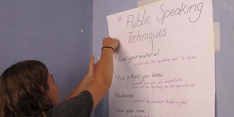 Kate putting up our Public Speaking poster in the office to remind us of the eight key points