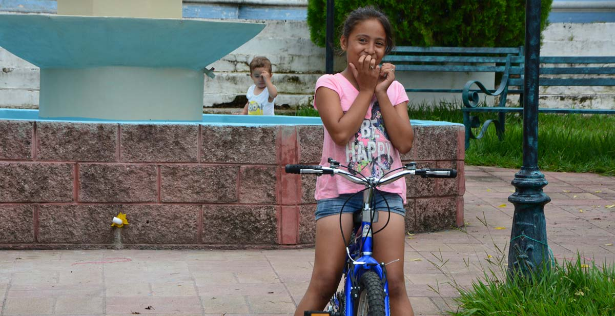 Local girl playing on a bicycle outside the Catholic Church