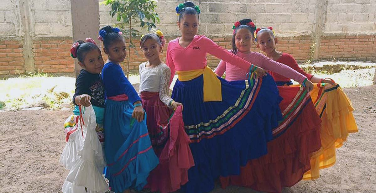 Pupils dressed in traditional Honduran dresses getting ready to go on stage