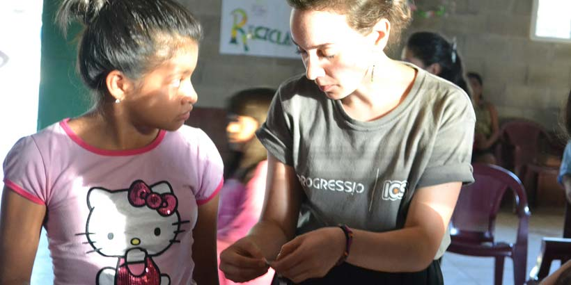 Giulia teaches a community member how to make jewellery with paper
