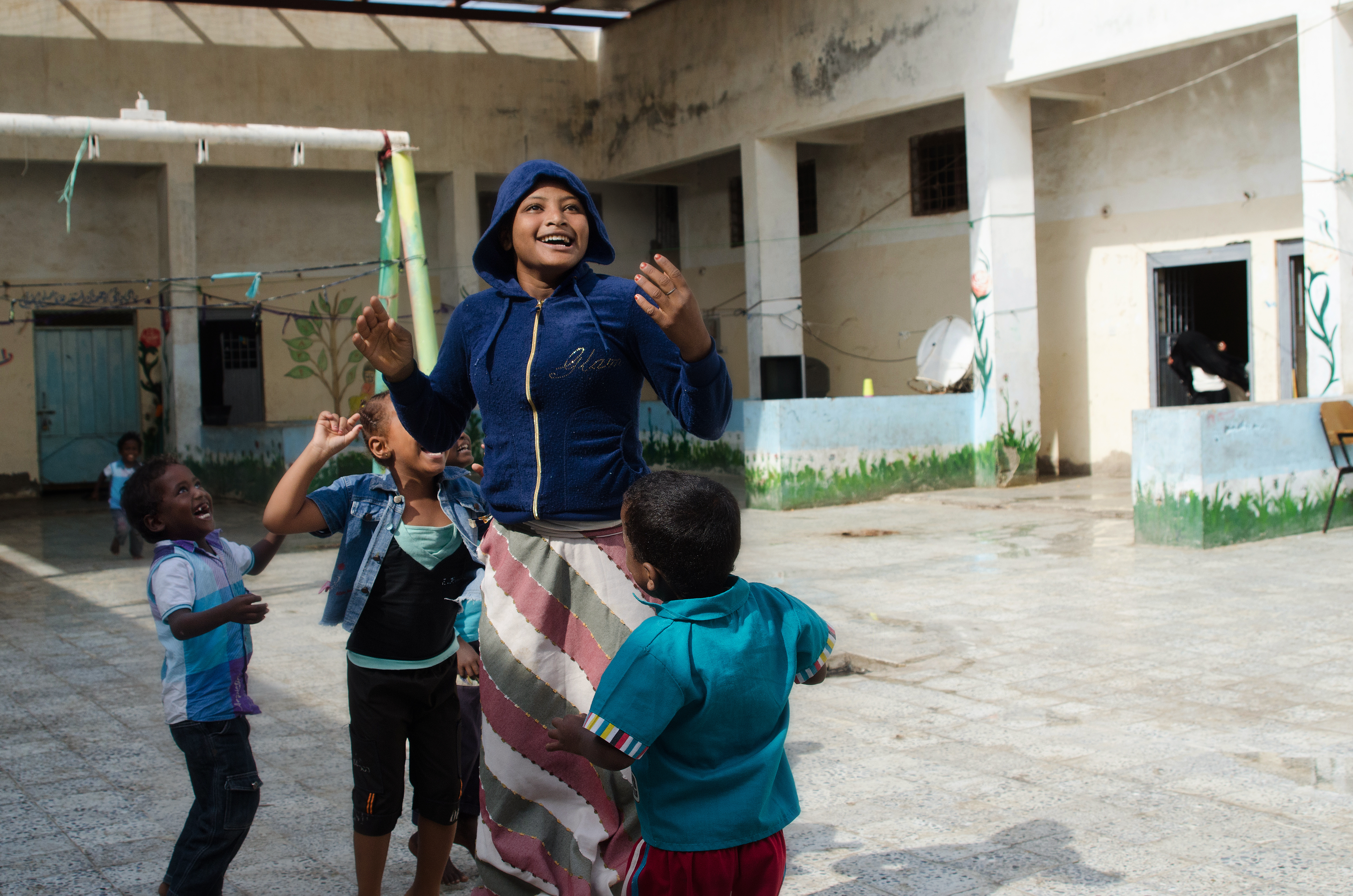 Saeeda, age 16, playing with children from Ethiopia and Eritrea in Hodeidah central prison. Saeeda has special needs, and was found by police and brought there as there's no other place for women in her situation. Photo: Amira Al-Sharif/Progressio 2014
