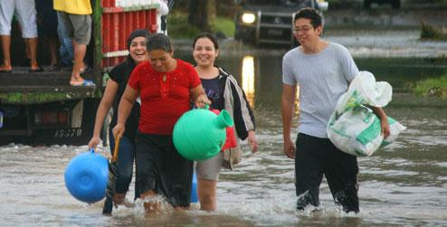 People wading through flood water in San Francisco Menendez, El Salvador