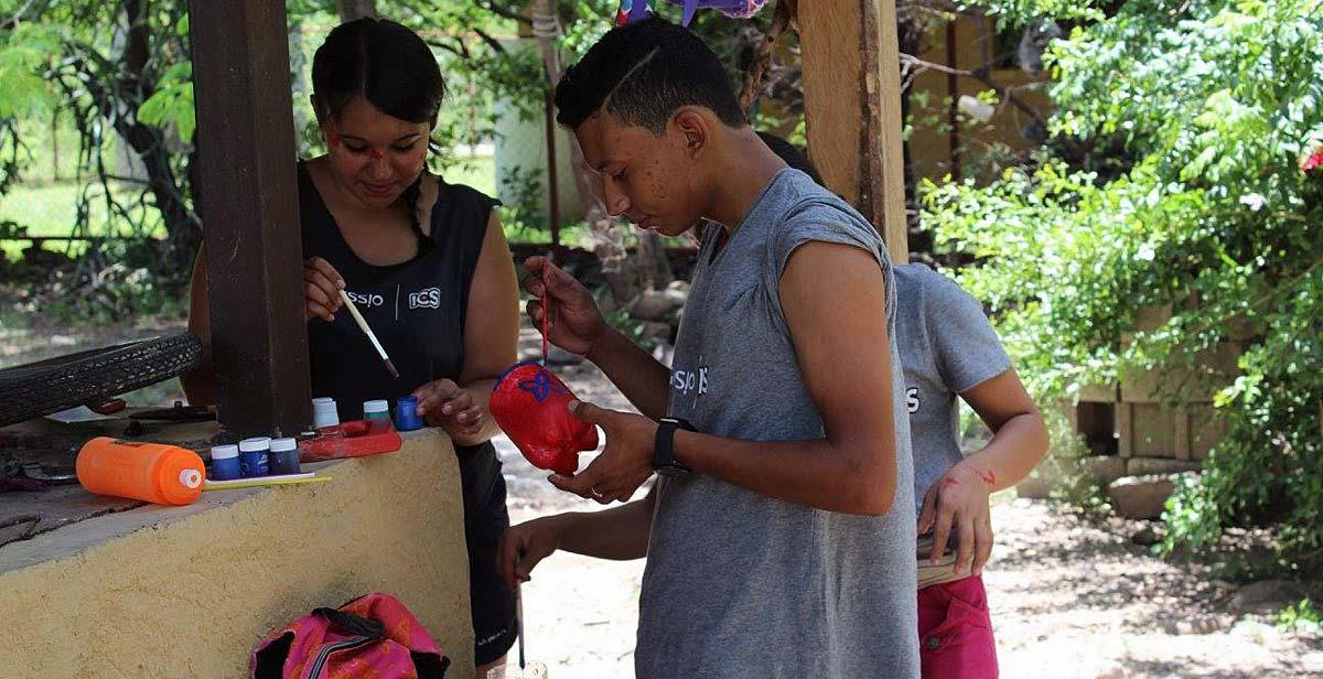 Volunteers painting plastic bottles