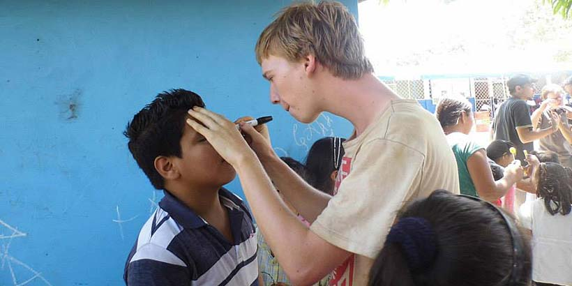 Matt engaging in face painting in a local school