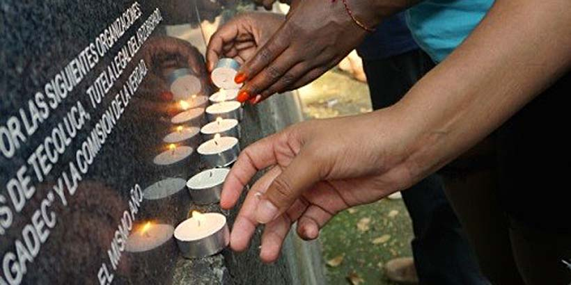 ICS volunteers lighting candles at the memorial