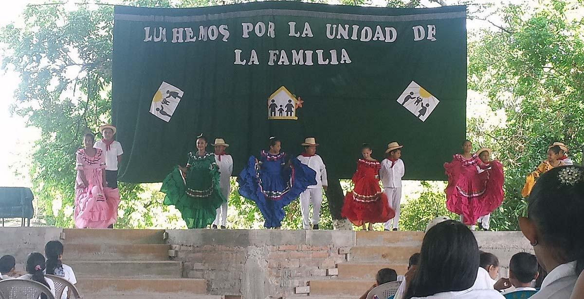 Children dancing a folkloric dance on stage for parents, teachers, and fellow pupils