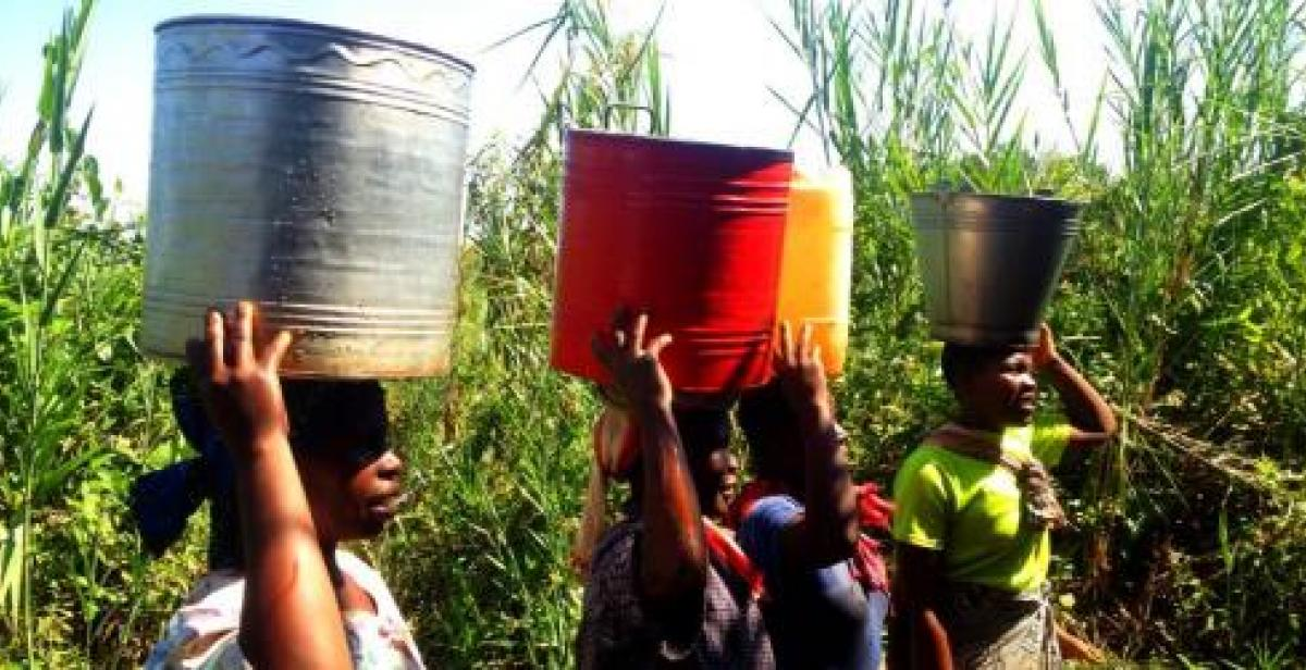 Women in Malawi carrying buckets on their heads