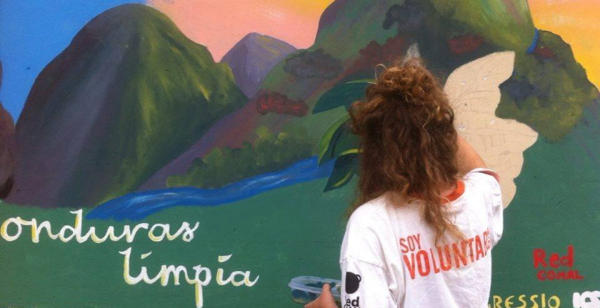 Volunteer painting a mural