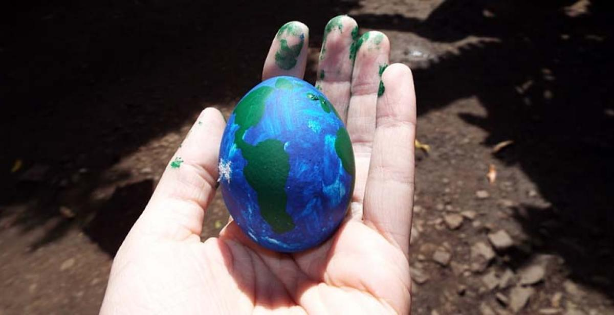 Egg painted like world in a hand