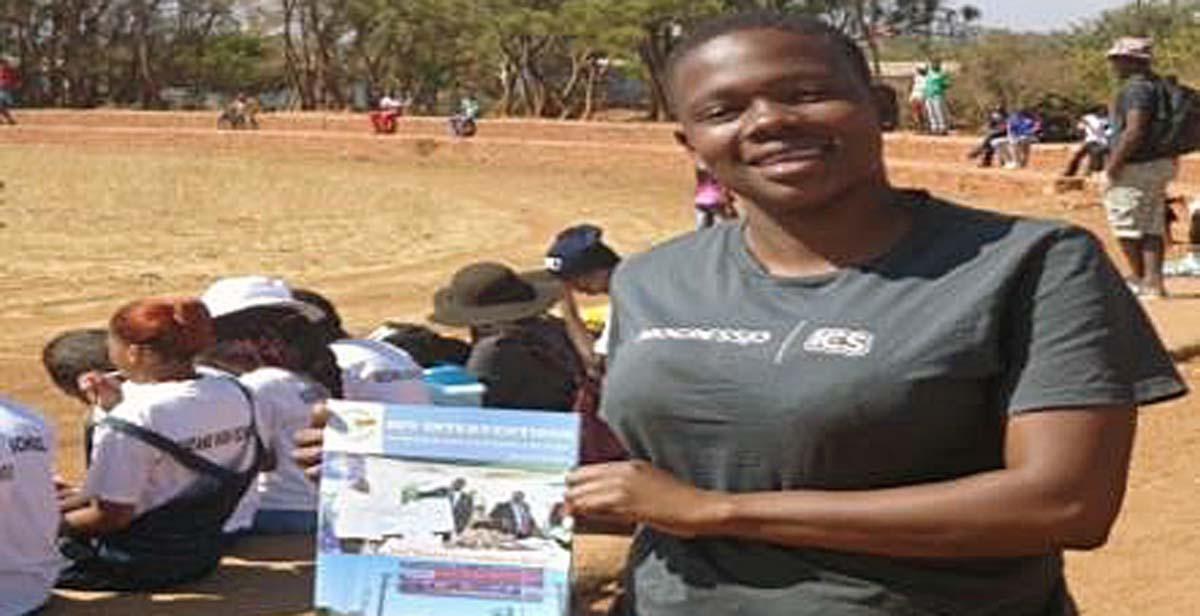 Holding a sample of books we were distributing during the Y.E.S League