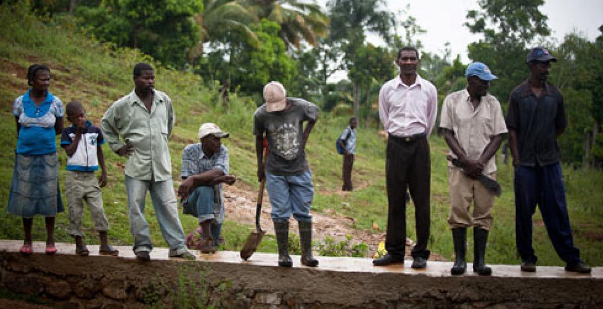 Villagers in Lamine Haiti standing on flood wall