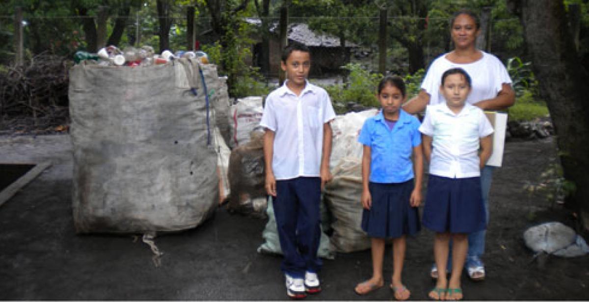 Children in El Salvador with bag of plastic bottles