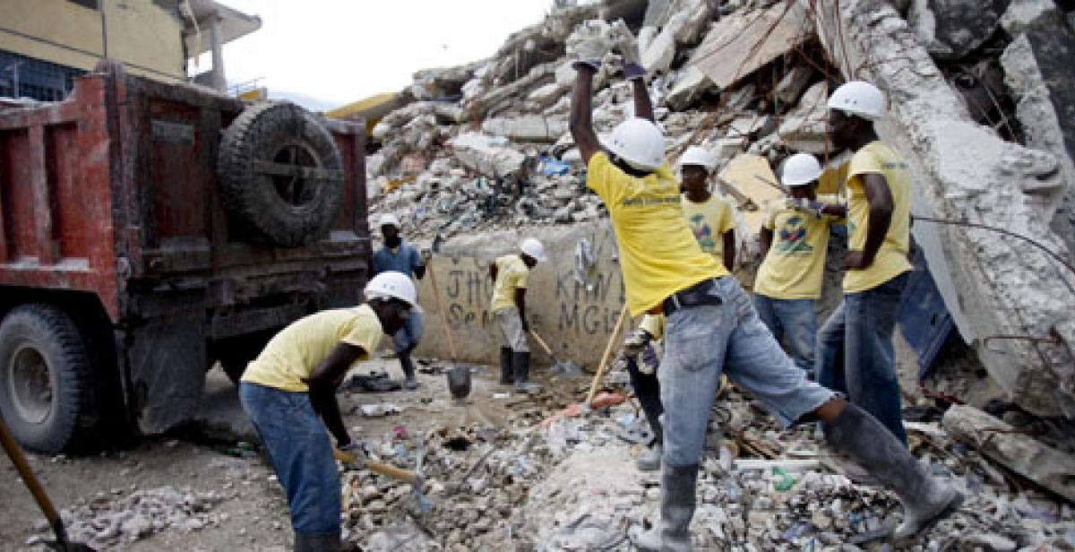 Haitians pile rubble into a waiting van
