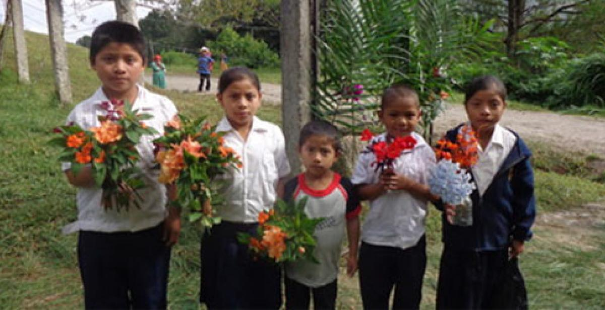 Children welcoming visitors with floweres