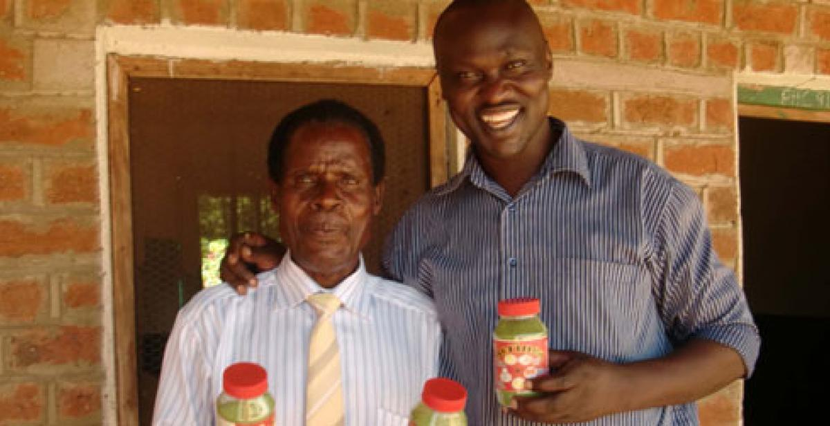 Innocent Ogaba and Mr Laston holding moringa jars