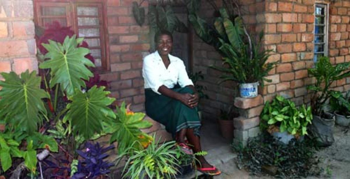 Portrait of Nifa Chumachiyenda, a farmer in Malawi, outside her house
