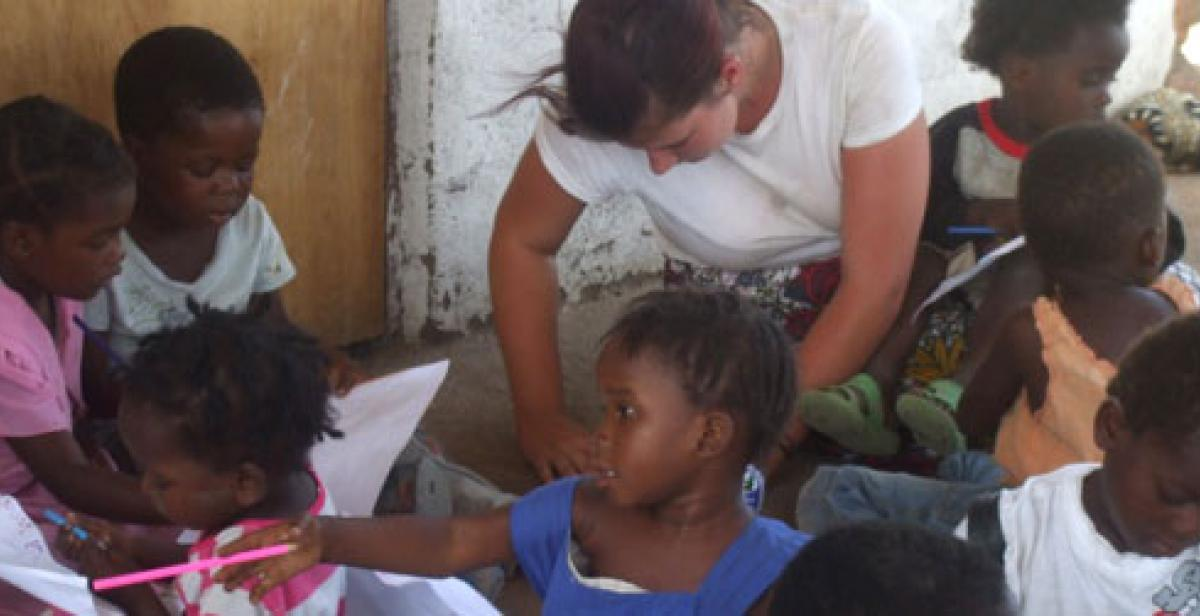 ICS volunteer Sammy drawing with children at community centre
