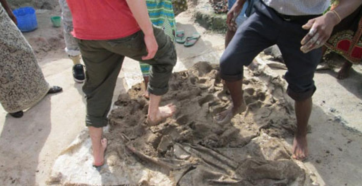 People kicking clay with their feet, Malawi