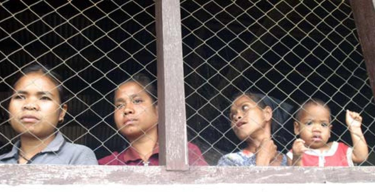 Women look through a wire screen at a window in Timor-Leste