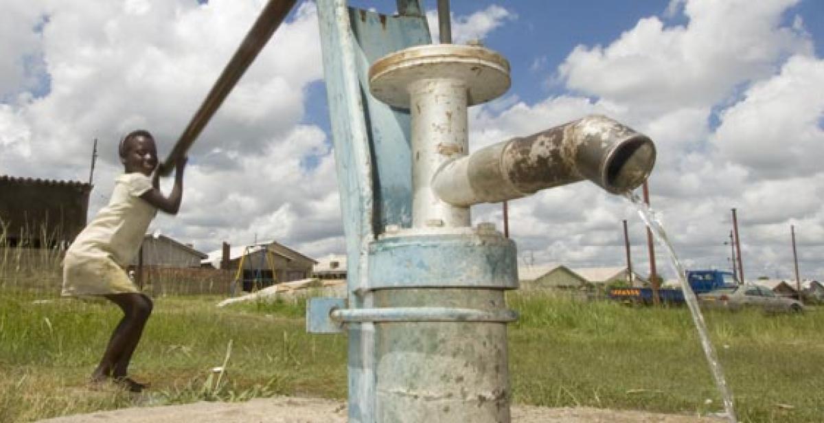 Virginia Jarusa using water pump in Zimbabwe village