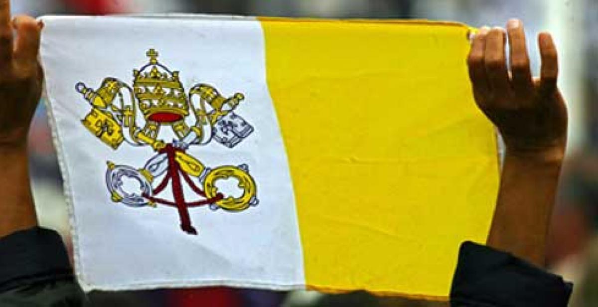 A Vatican flag is held aloft