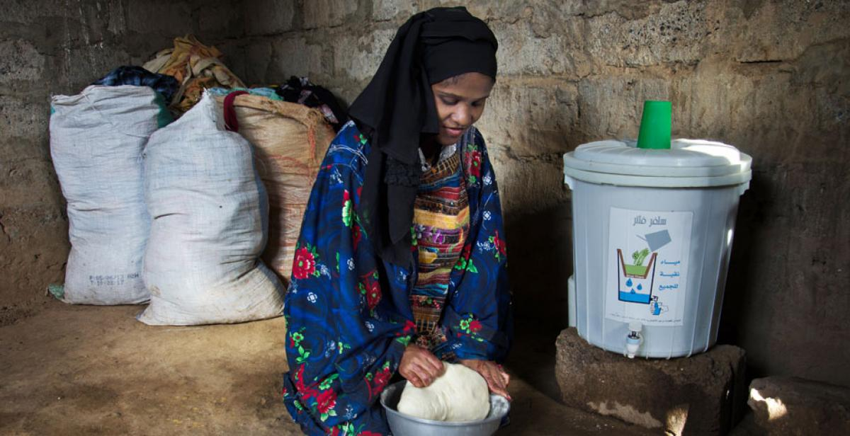 Haifa Ayash preparing dough next to a water filter, Zabid, Yemen