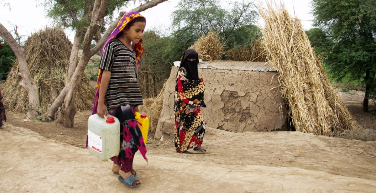 Rabab Aziz, age 7, carrying water to her family house from the village well