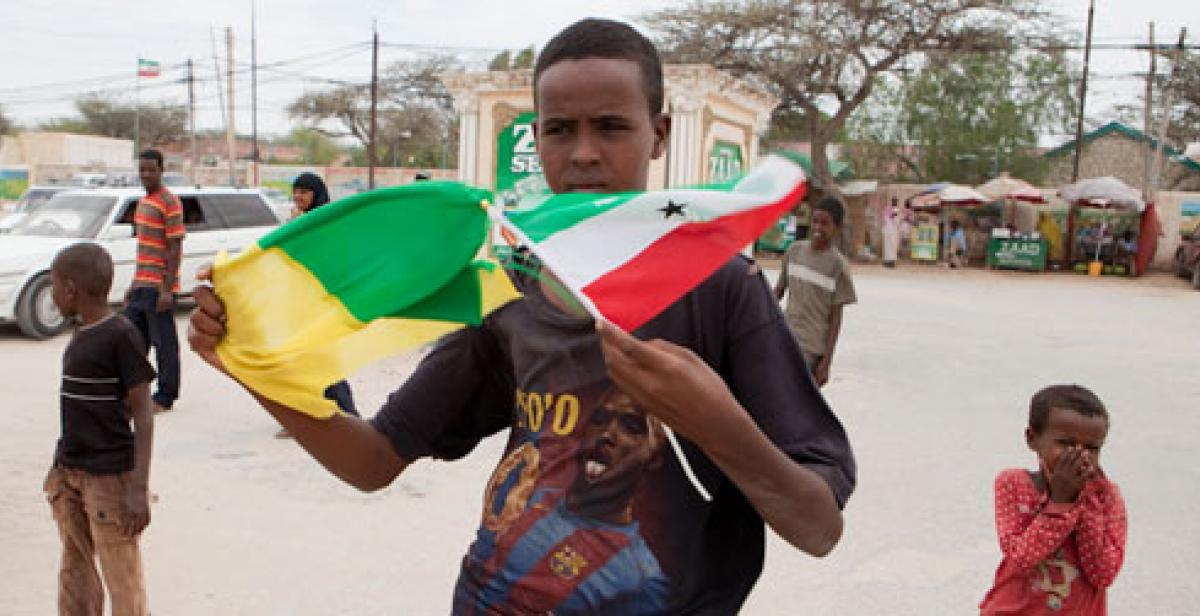 A young man holds flags on a Hargeisa street
