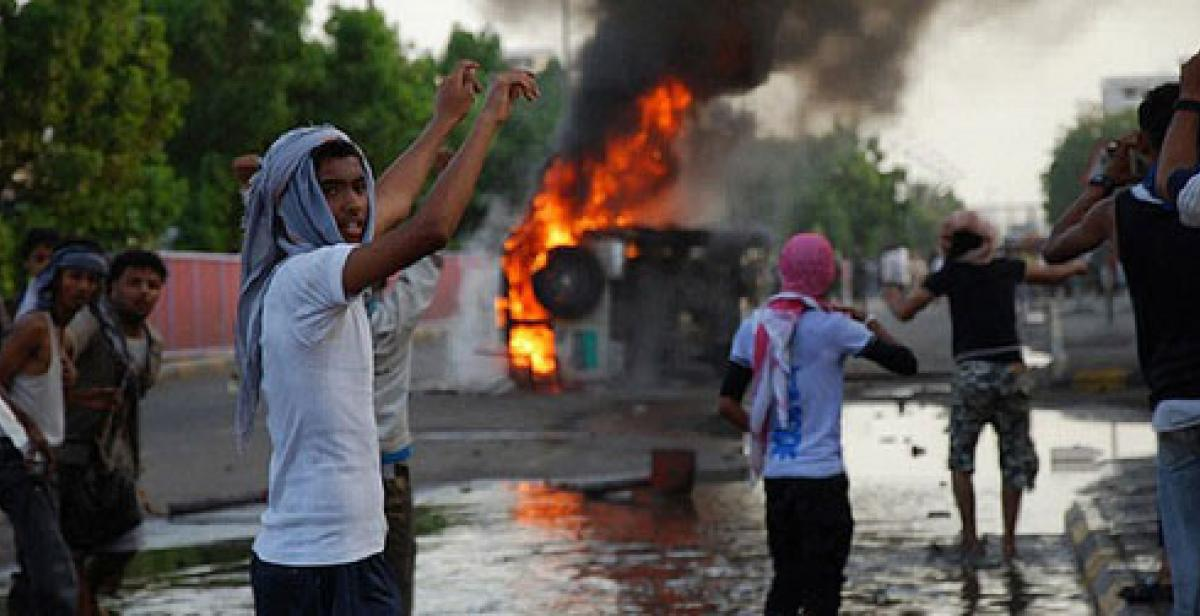 People protest in front of burning vehicle in Aden Yemen