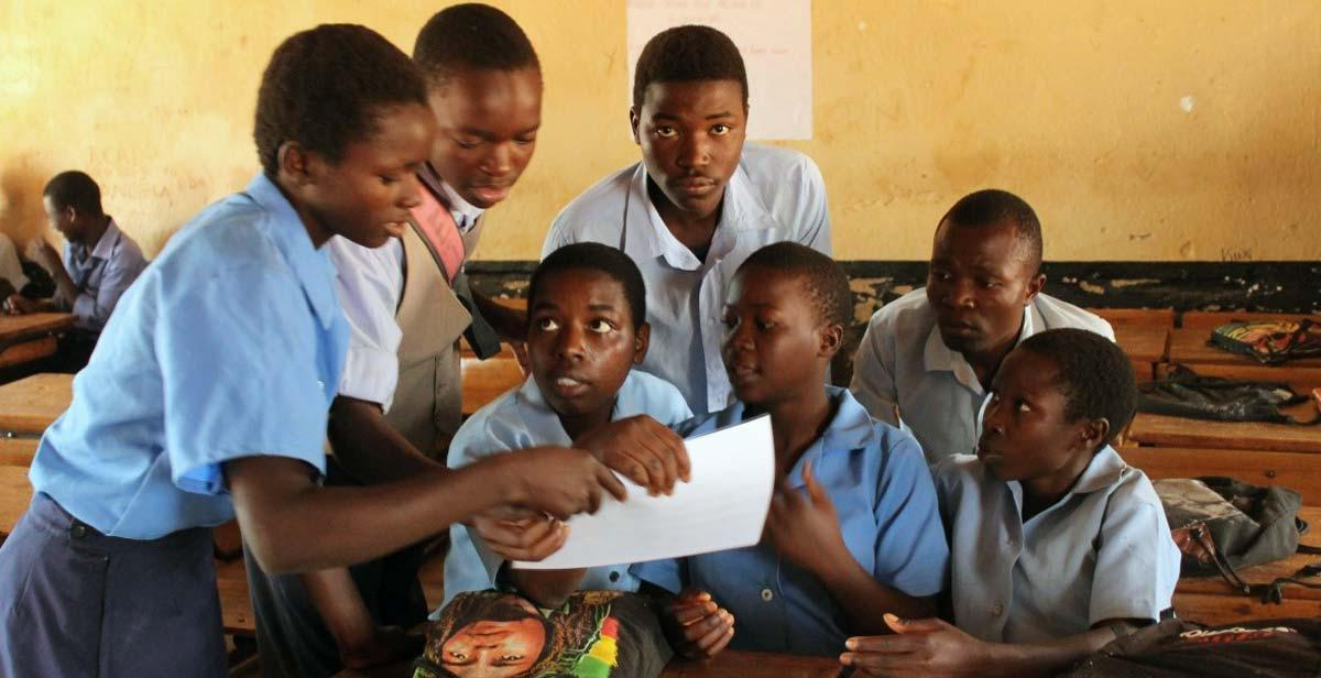 Students at Baula CDSS looking over pictures on STIs