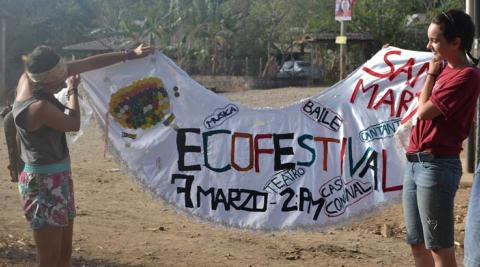 Elza and Giulia show the banner that the Eco-festival Promotion Group proudly created using cloth and other recycled materials