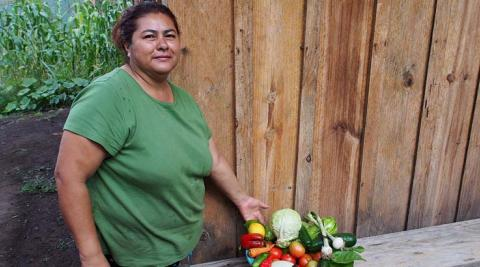 Gladys with her veg grown from seeds given by ASOMUPRO