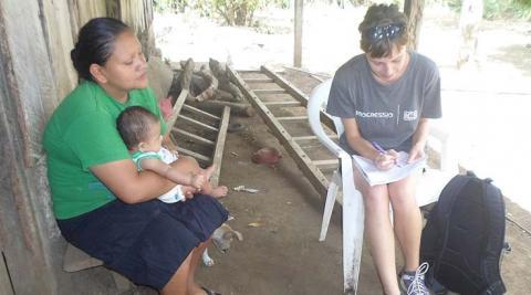 An ICS volunteer surveying community members