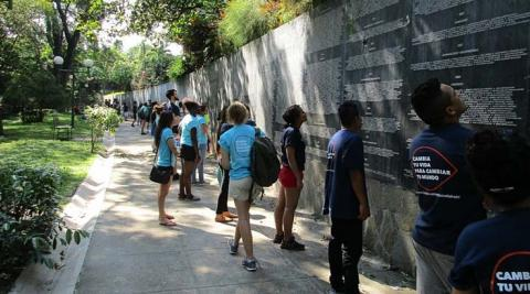 ICS volunteers reading the names of the killed and missing on the memorial plaque in Parque Cuscatlán