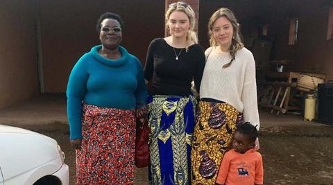 Jessica and Niamh wearing chitenjes with their host mum and host niece