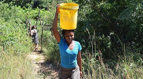Takudzwa (a national volunteer) bringing water up from the Odzi River to water the garden