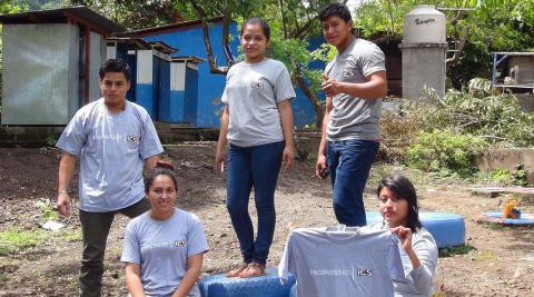 Michael (holding the t-shirt) with fellow ICS national alumni volunteering in the construction of the schools' playground area