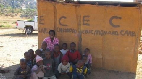 A Zimbabwean teacher sits in front of her school with he4r pupils
