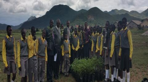 Teachers and School Children stand in front of donated trees