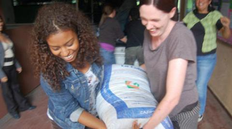 Two Progressio volunteers carry a sack of emergency supplies