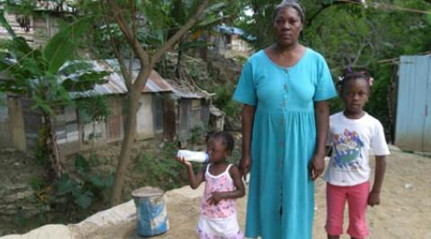 A woman and her children in front of a house in Santiago, Dominican Republic