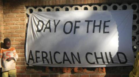 Boy stands beside 'Day of the African Child' banner