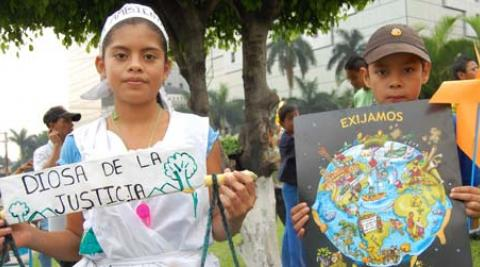 Young participants holding banners at Earth Day march in El Salvador