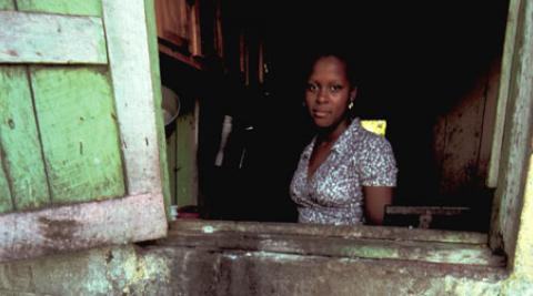 Haitian woman looking out of house window